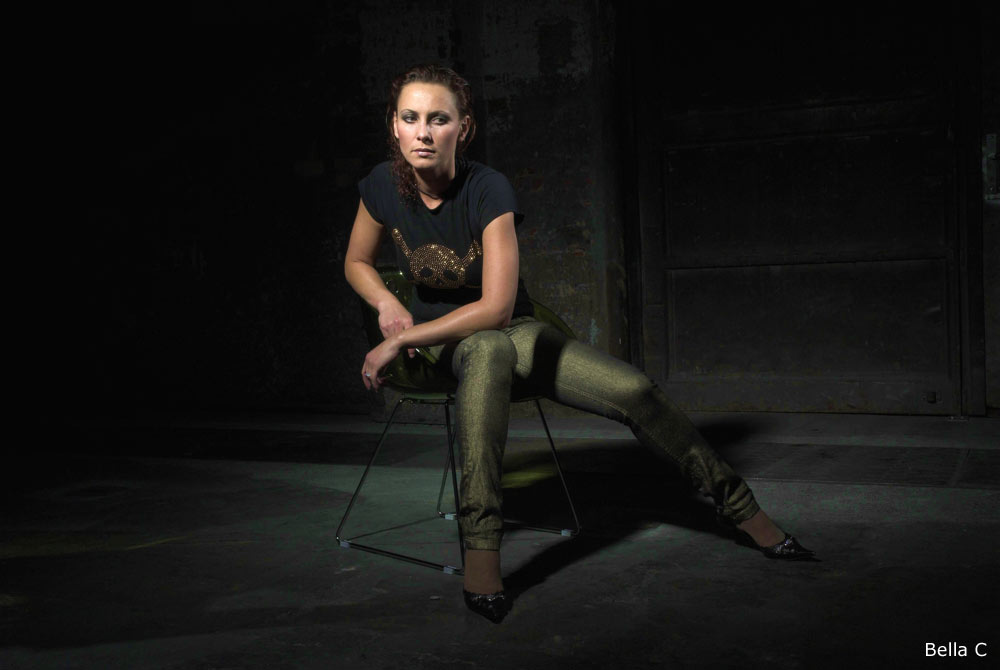 Bella C sitting with tight trousers and black golden shirt