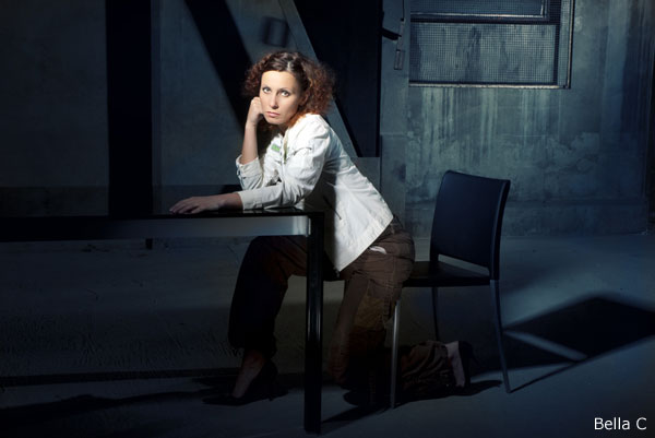Bella C with with white jacket and brown trousers sitting on chair