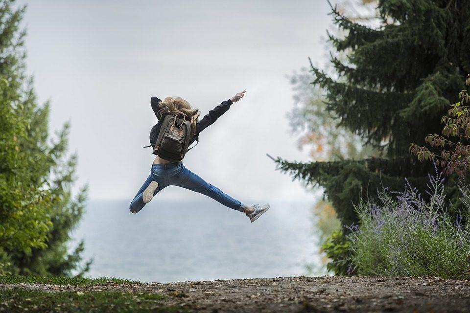 Frau springt in der vor Freude in die Luft